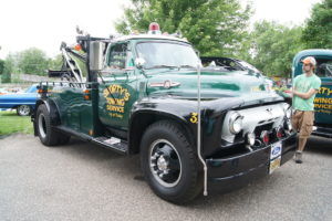 towing company truck that is a classic and green color